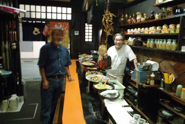 僕がもう30年ほど通っている琉球料理の店で。2代目の主人と歓談する小橋川さん。