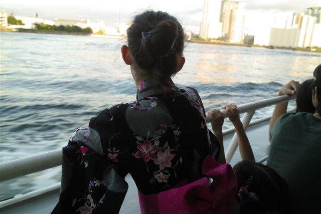 浴衣姿で隅田川の夕景を見つめる少女。