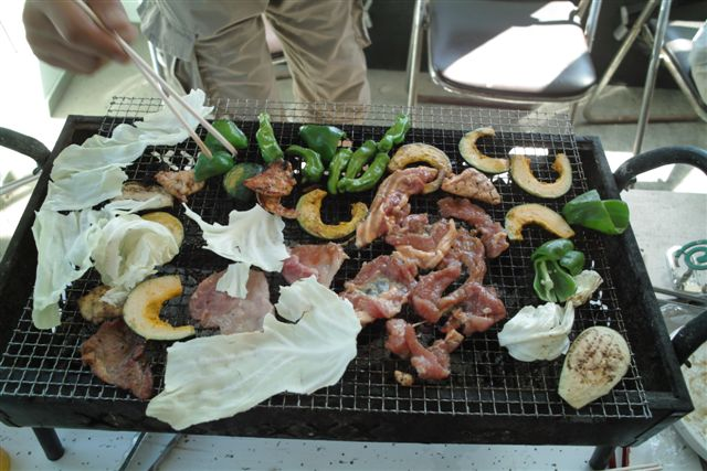 炭火を熾して家で作っている野菜と豚や鶏を網で焼く。このほかに自家製のトマトやスイカ、糠漬けのキュウリなどご馳走が盛りだくさん。