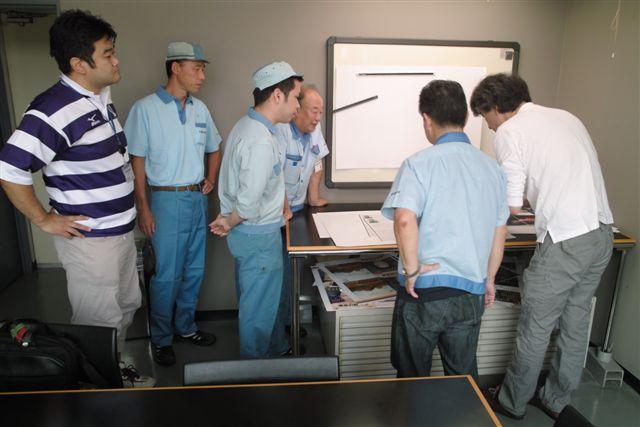 印刷現場の技術者たちと刷りを検討するK編集者。