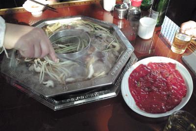 12月8日。綿陽の街で昼食。たくさんの茸と牛の生肉の鍋料理が旨かった。
